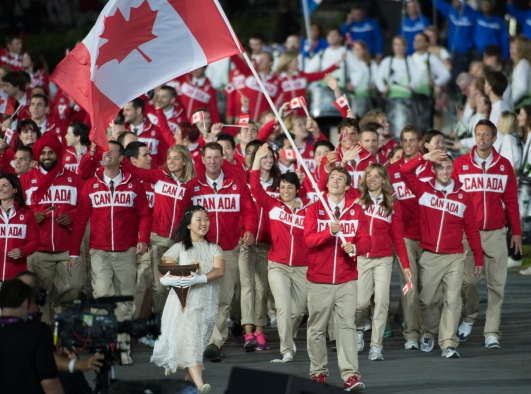 Canadians walking wearing red and waving Canadian flag