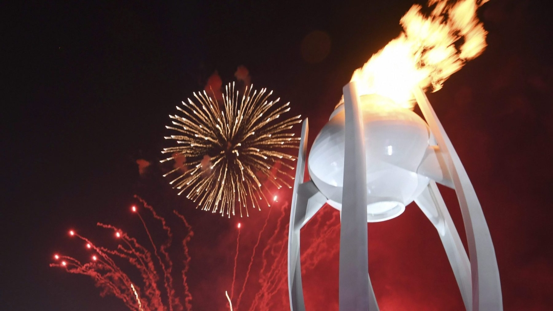 Fireworks explode behind the Olympic flame during the opening ceremony of the 2018 Winter Olympics in Pyeongchang,