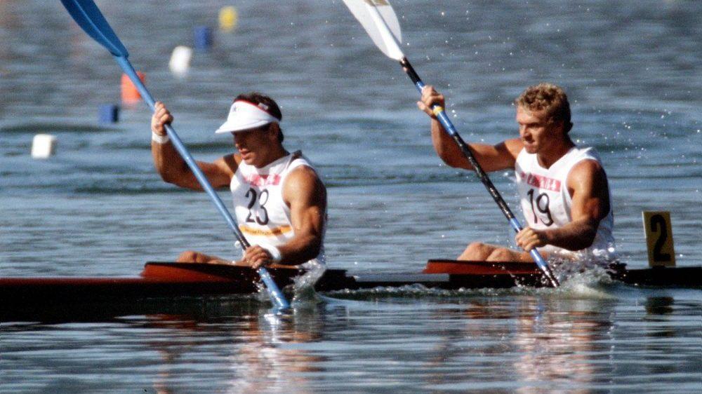 Alwyn Morri and Hugh Fisher paddling in the water.