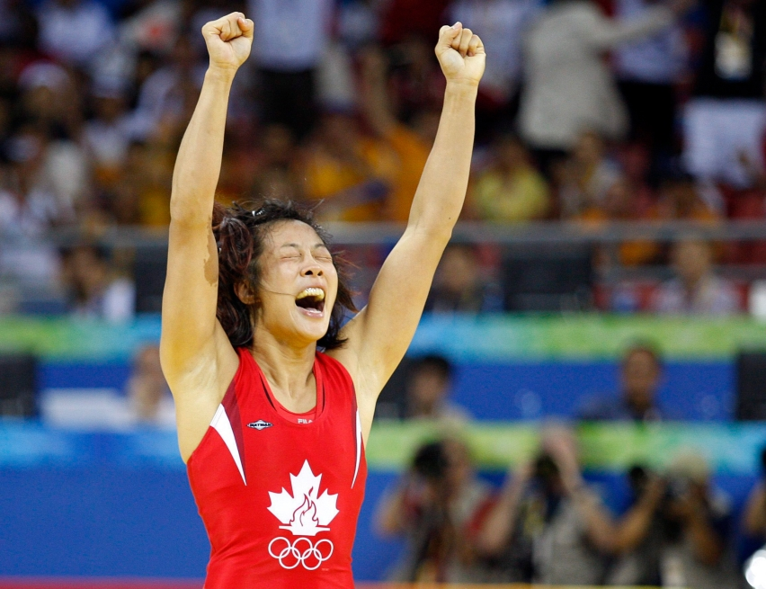Canada's Carol Huynh from Hazelton, B.C. celebatres her gold medal victory over Chiharu Icho from Japan in the women's freestyle 48kg wrestling final at the Beijing 2008 Summer Olympics in Beijing, Saturday, August 16, 2008. THE CANADIAN PRESS/Paul Chiasson