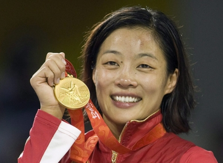 Canada's Carol Huynh from Hazelton, B.C. holds up her gold medal for the women's freestyle 48kg wrestling during victory ceremonies at the Beijing 2008 Summer Olympics in Beijing, Saturday, August 16, 2008. THE CANADIAN PRESS/Paul Chiasson