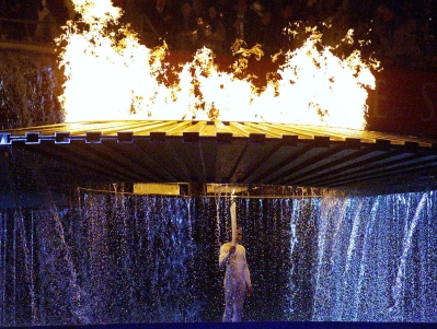Cathy Freeman stands under the Olympic torch after lighting the flame at the opening ceremonies for the 2000 Summer Olympics in Sydney. (CP PHOTO/Kevin Frayer)