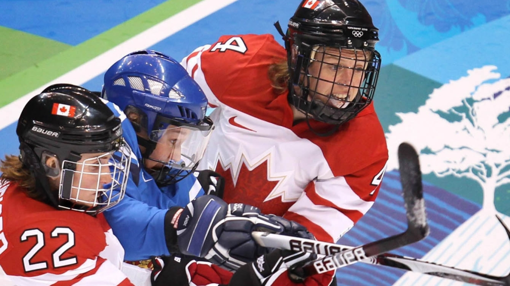 Hayley Wickenheiser and Becky Kellar fight for control of the puck with Finland's Karoliina Rantamaki