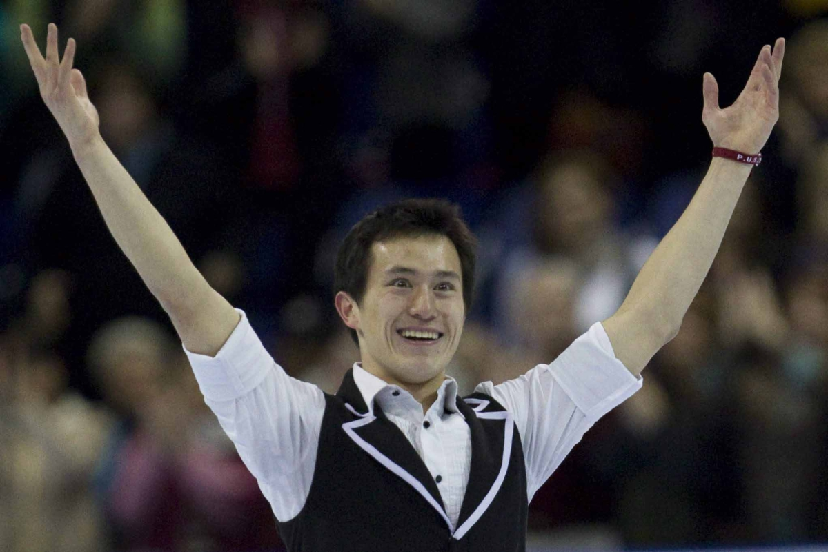 Patrick Chan smiling with his arms in the air