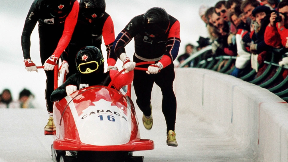 Four men running with bobsleigh
