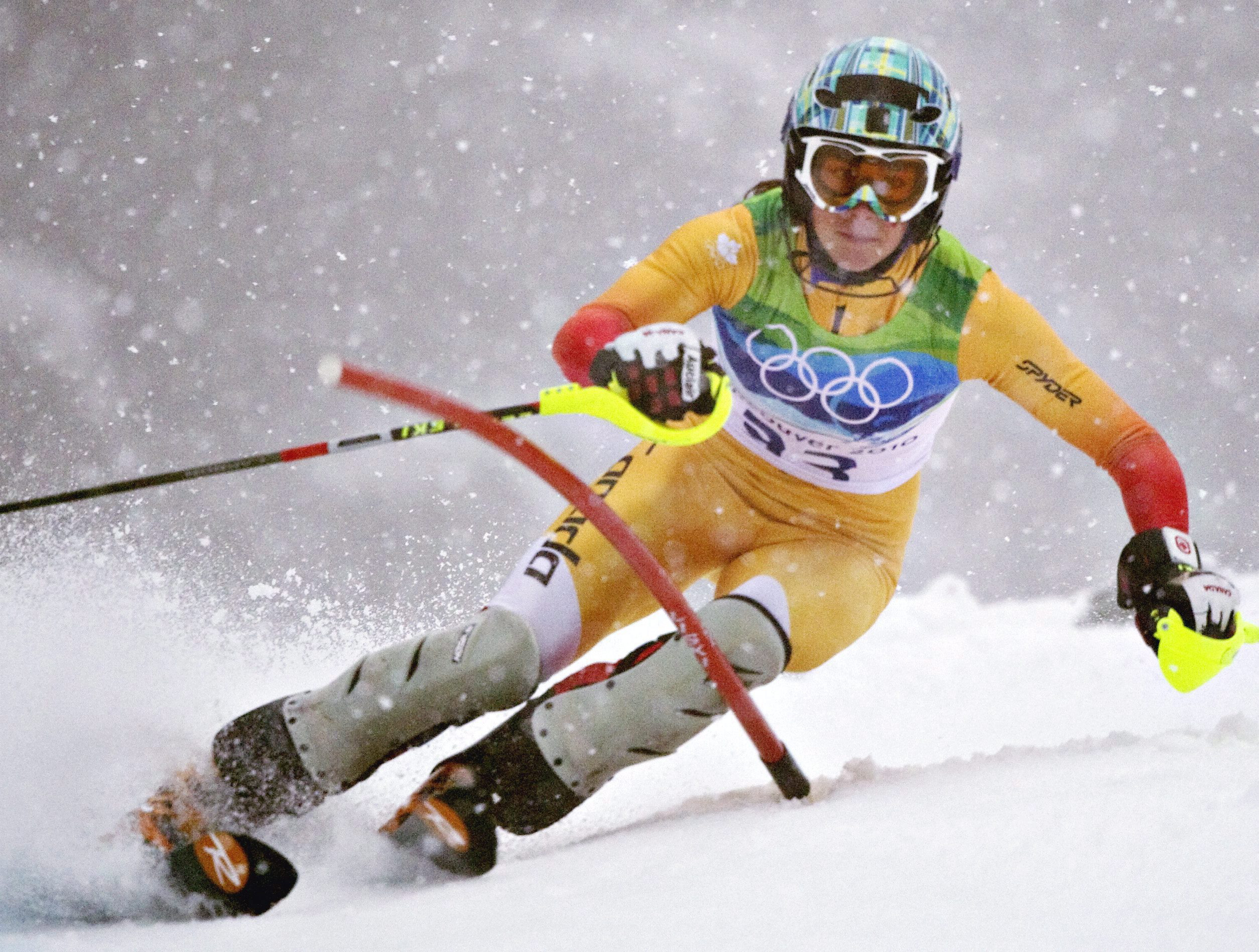 An alpine skier goes around a slalom gate