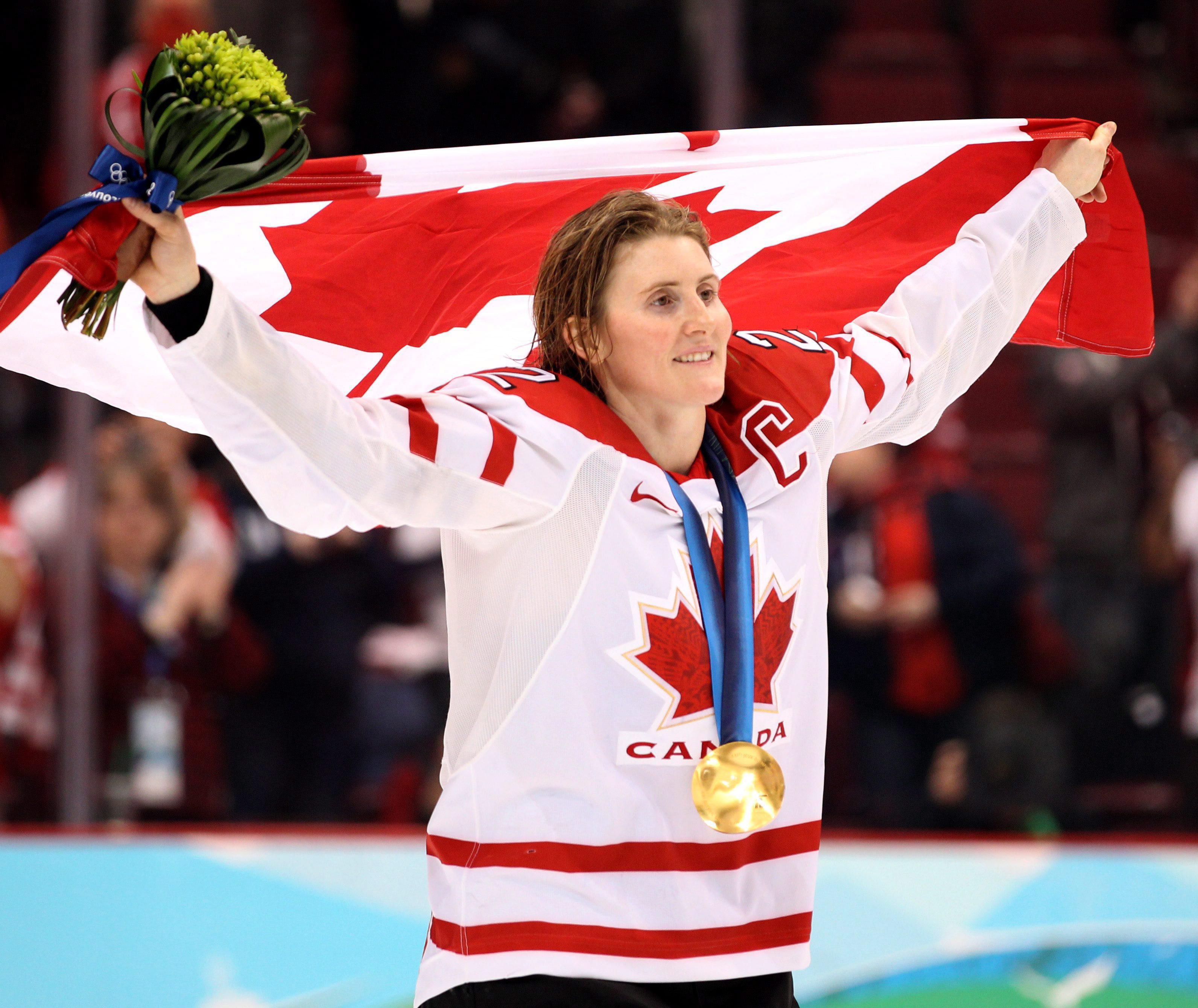 Wickenheiser on skates holding Canadian flag