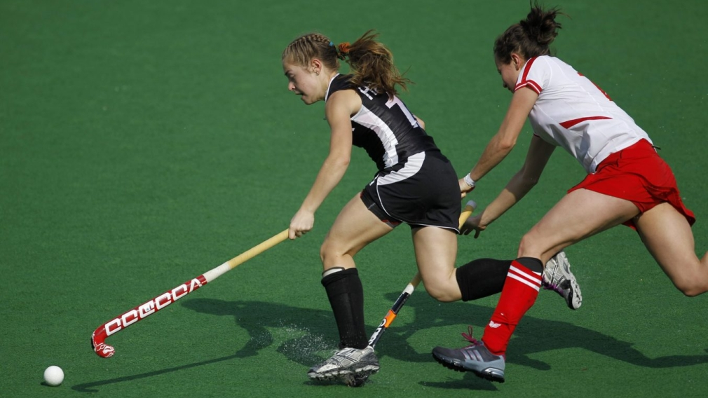 Canada's Hannah Haughn, left, is caught on the foot by Martyna Gabar of Poland during their field hockey Olympic qualifier in New Delhi, India,