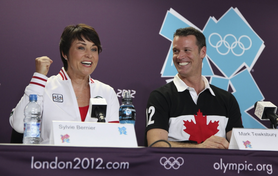 Sylvie Bernier and Mark Tewksbury sit at a press conference table