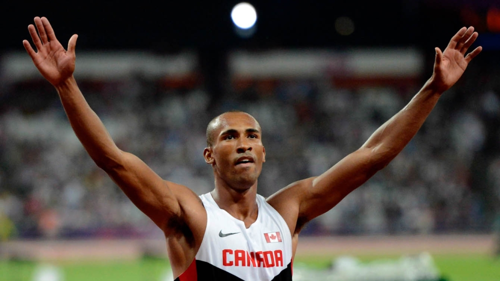 Damian Warner poses with both his hands in the air