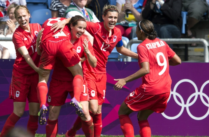 Canada forward Christine Sinclair (12), defender Rhian Wilkinson (7) and midfielder Brittany Timko (left) and defender Candace Chapman (9) hoist midfileder Diana Matheson into the air after she scored the game winning goal against France in second half Bronze medal football action at the Olympic Games in Coventry, Great Britain on Thursday August 9, 2012. THE CANADIAN PRESS/Frank Gunn