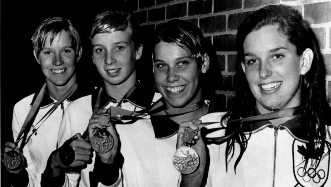 A black and white photo of four female swimmers holding up Olympic medals.