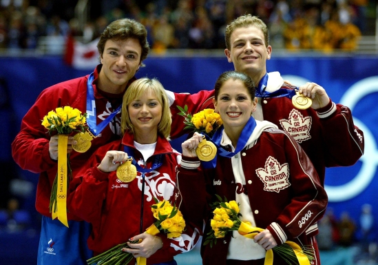 Gold medalists David Pelletier and Jamie Sale stand next to Russians Anton Sikharulidze and Elena Berezhnaya as they show off thier gold medals Sunday Feb. 17, at the 2002 Olympic Winter Games. (CP Photo/HO/COC/Andre Forget)