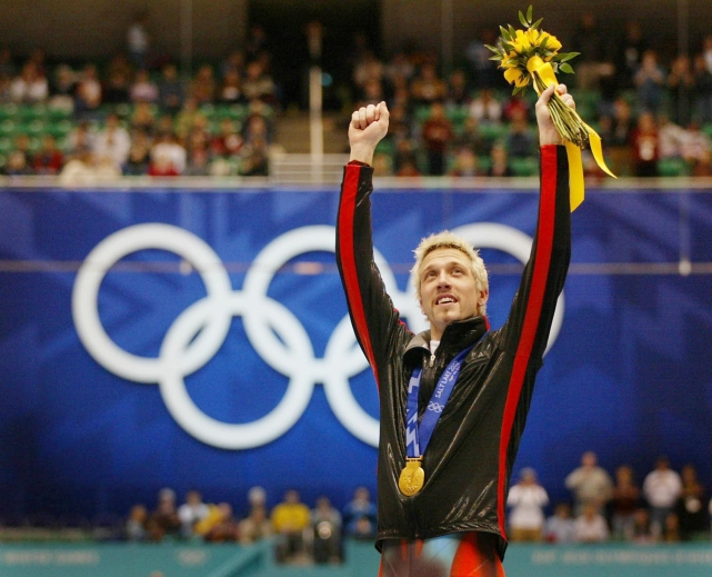 Marc Gagnon with arms raised on podium