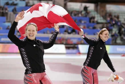 Gold medallist Canada's Cindy Klassen, left, and silver medalist, teammate Kristina Groves, skate around the oval with the Canadian flag following the womens 1,500 metre speedskating competition at the Turin 2006 Winter Olympic Games Wednesday, Feb. 22, 2006 in Turin. (CP PHOTO/Paul Chiasson)