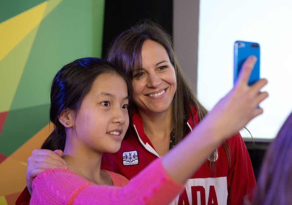 A fan takes a picture with a Team Canada athlete