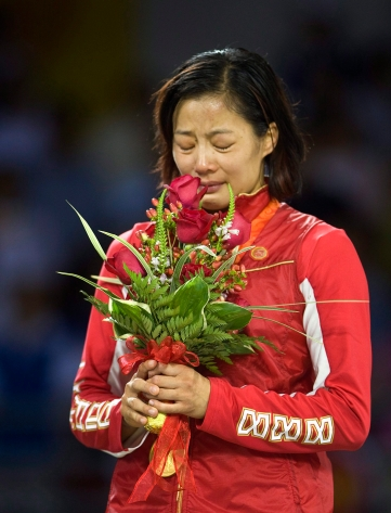 Canada's Carol Huynh from Hazelton, B.C., gold medalist in the women's freestyle 48kg wrestling, fights back tears during the national anthem during victory ceremonies at the Beijing 2008 Summer Olympics in Beijing, Saturday, August 16, 2008. THE CANADIAN PRESS/Paul Chiasson