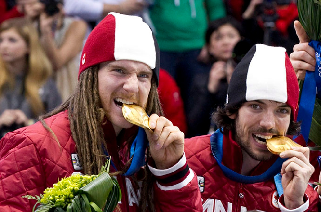 Olivier Jean and Charles Hamelin bite their 5000m relay gold medals at Vancouver 2010 THE CANADIAN PRESS/Paul Chiasson
