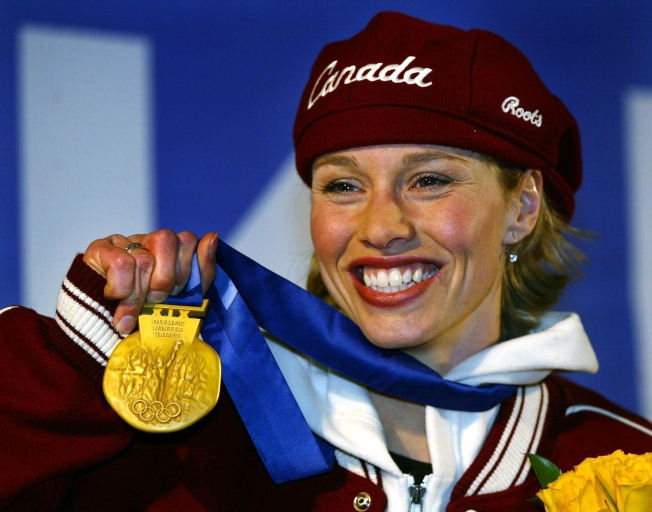 Canadian gold medallist in the women's 500m speed skating, Catriona Le May Doan, shows off her medal in Salt Lake City, Utah Friday Feb. 15, at the 2002 Olympic Winter Games. (CP PHOTO/HO/COC/Andre Forget)