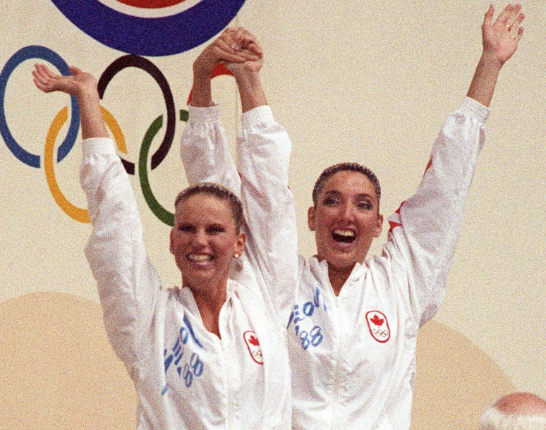 Carolyn Waldo and Michelle Cameron raise their arms in celebration