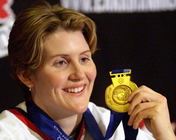 Canadian women's hockey team member Hayley Wickenheiser shows off her Olympic gold medal at a press conference in Calgary Wednesday Feb. 27, 2002. (CP PHOTO/Jeff McIntosh)