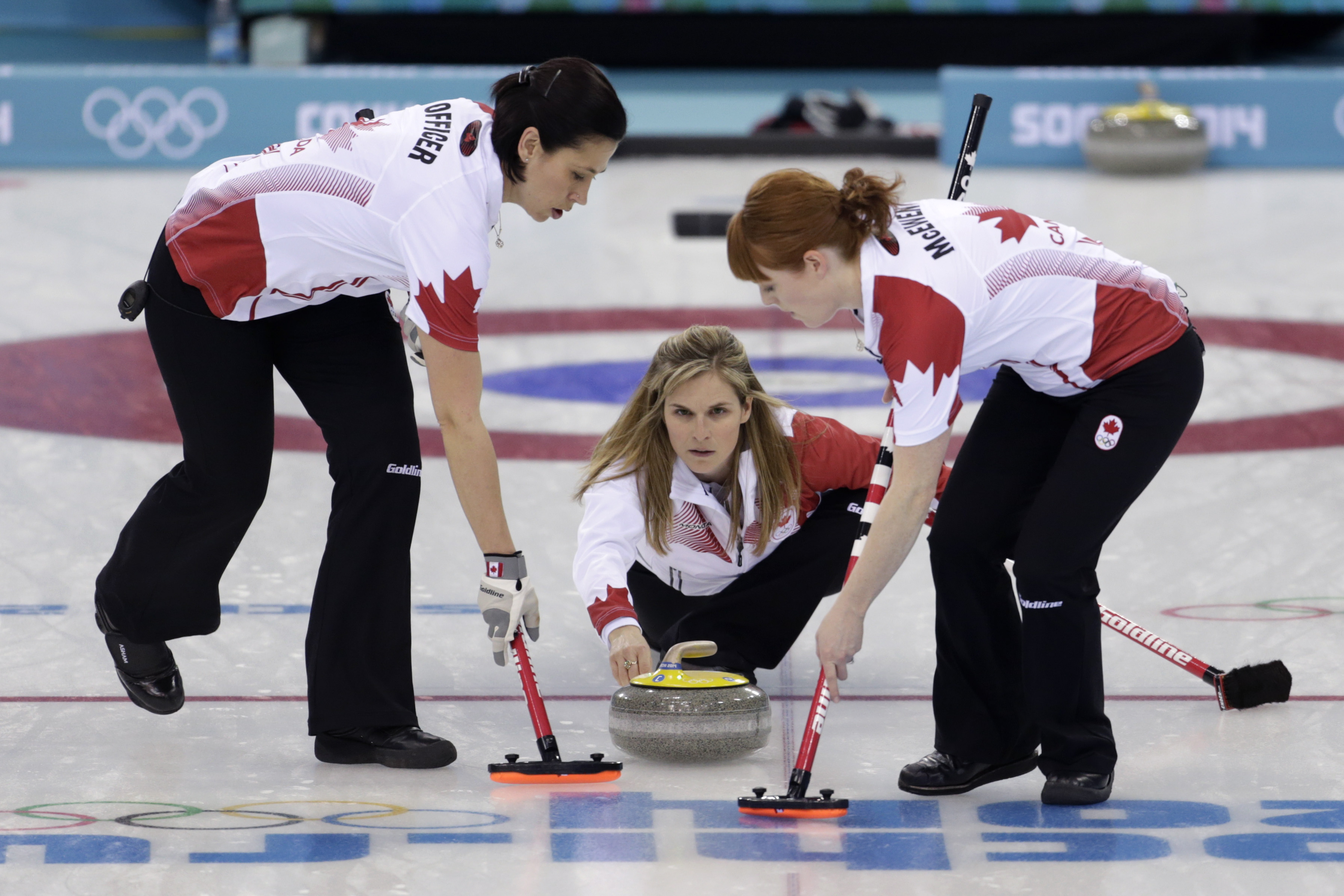 Jennifer Jones throws a stone to be swept by her teammates