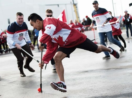 Speed skater Gilmore Junio takes a shot in a friendly ball hockey between Canada and the USA on February 19, 2014 at the 2014 Olympic Winter Games.