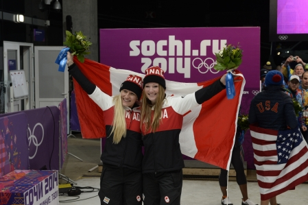 Kaillie Humphries and Heather Moyse celebrating with the Canadian flag