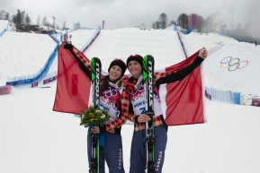 Kelsey Serwa and Marielle Thompson holding the Canadian flag behind them