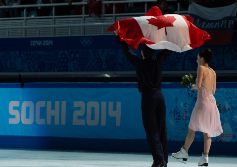 Tessa and Scott celebrate while holding the Canadian flag
