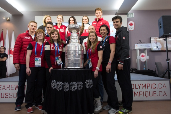 People posing for a picture with the Stanley Cup
