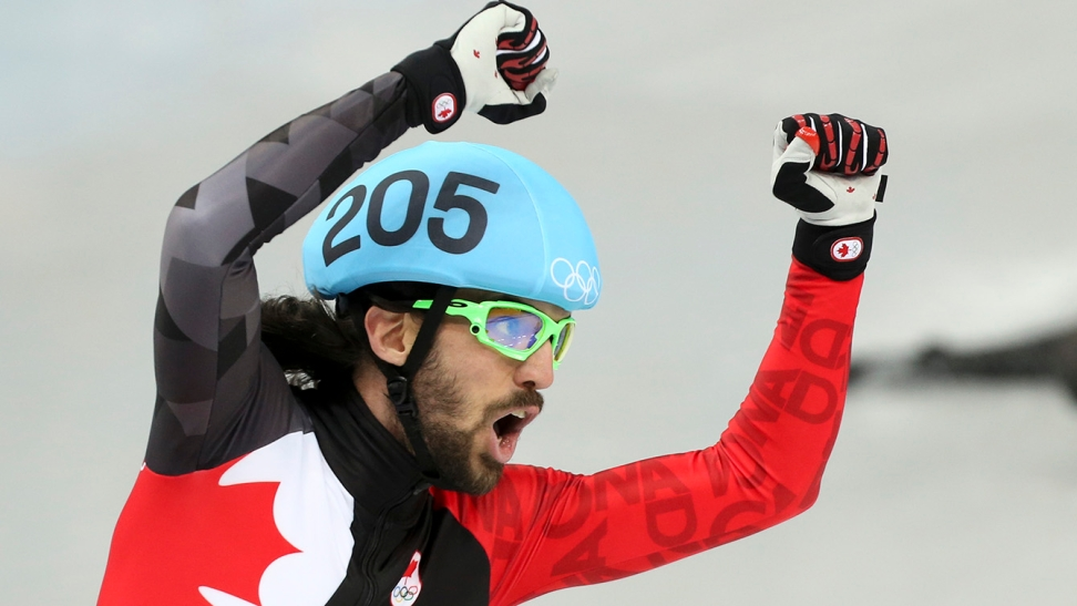 Charles Hamelin celebrates winning his third career Olympic gold medal after finishing first in the 1500m at Sochi 2014.