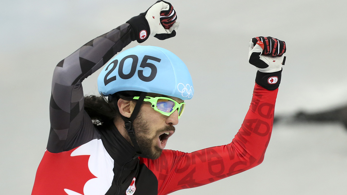 Charles Hamelin celebrates with a Canadian flag after winning 1500m gold.