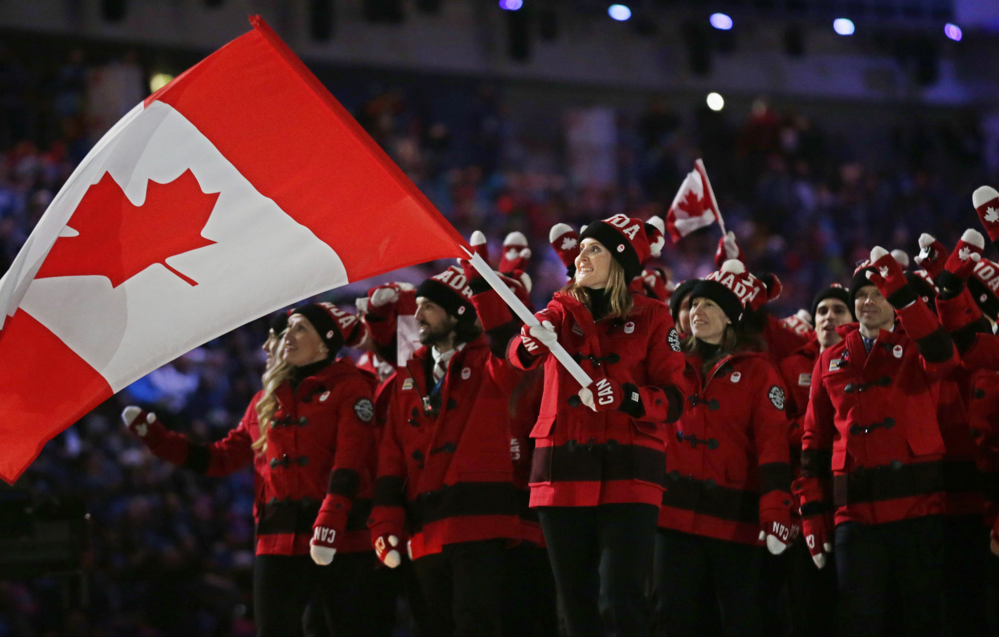 Hayley Wickenheiser of Canada carries her country flag as they arrive during the opening ceremony of the 2014 Winter Olympics in Sochi, Russia, Friday, Feb. 7, 2014. (AP Photo/Matt Dunham)
