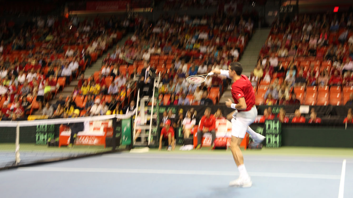 Raonic delivers an overhead volley to finish a first set rally against Gonzalez.
