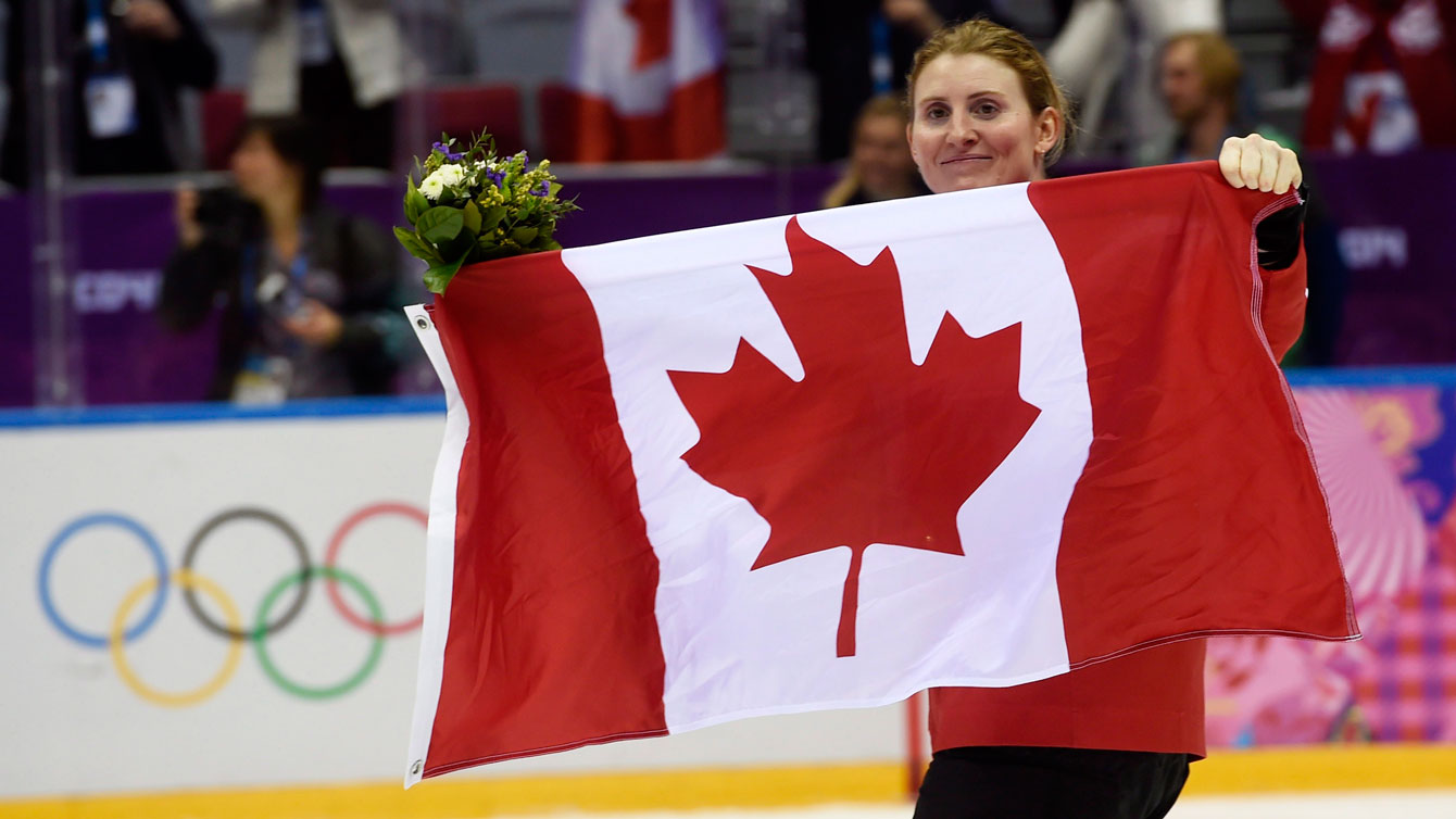 Hayley Wickenheiser skates with the Canadian flag after the gold medal game in Sochi.