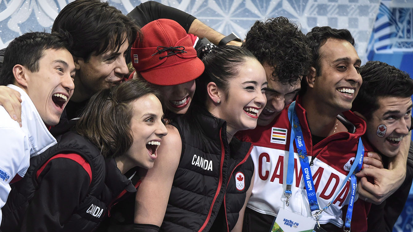 Canada's figure skating team congratulate Kaetlyn Osmond after a performance in the team event.