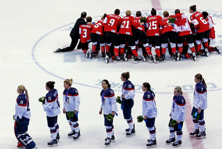Canadian women pose for championship photo after a stunning comeback as the United States team skates away.