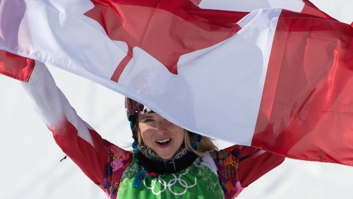 Dominique Maltais celebrates with the flag after her medal-winning run.
