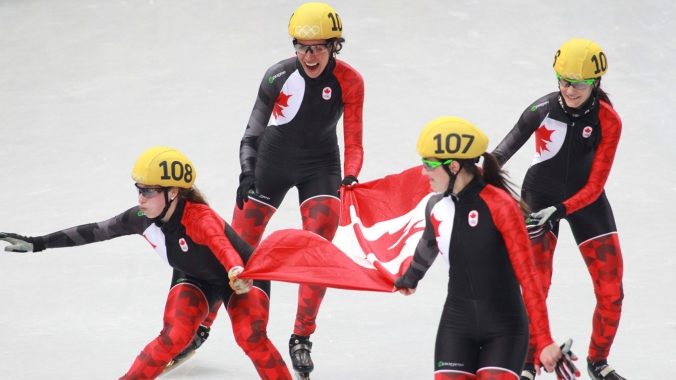Short track team skates with the flag following the final result, a silver for Canada as China was disqualified.
