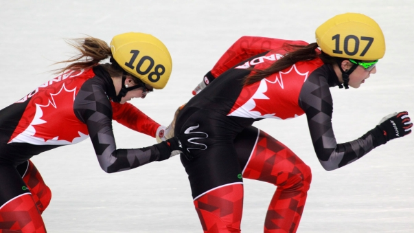 Marianne St-Gelais pushes Valérie Maltais as they tag up during the 3000m relay final at Sochi 2014.