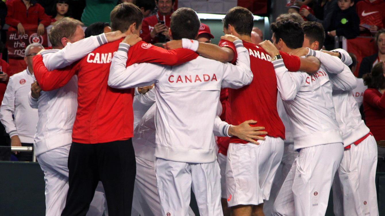 Canadian team of Milos Raonic, Vasek Pospisil, Daniel Nestor and Frank Dancevic celebrate the win over Japan with coaches and some team staff.