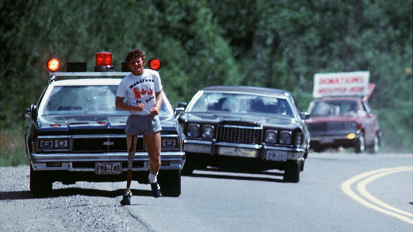 """Terry Fox received Ontario Provincial Police escort while he ran through Ontario. In the photo, the third car in the convoy has a sign that reads """"Donations Accepted Here."""""""