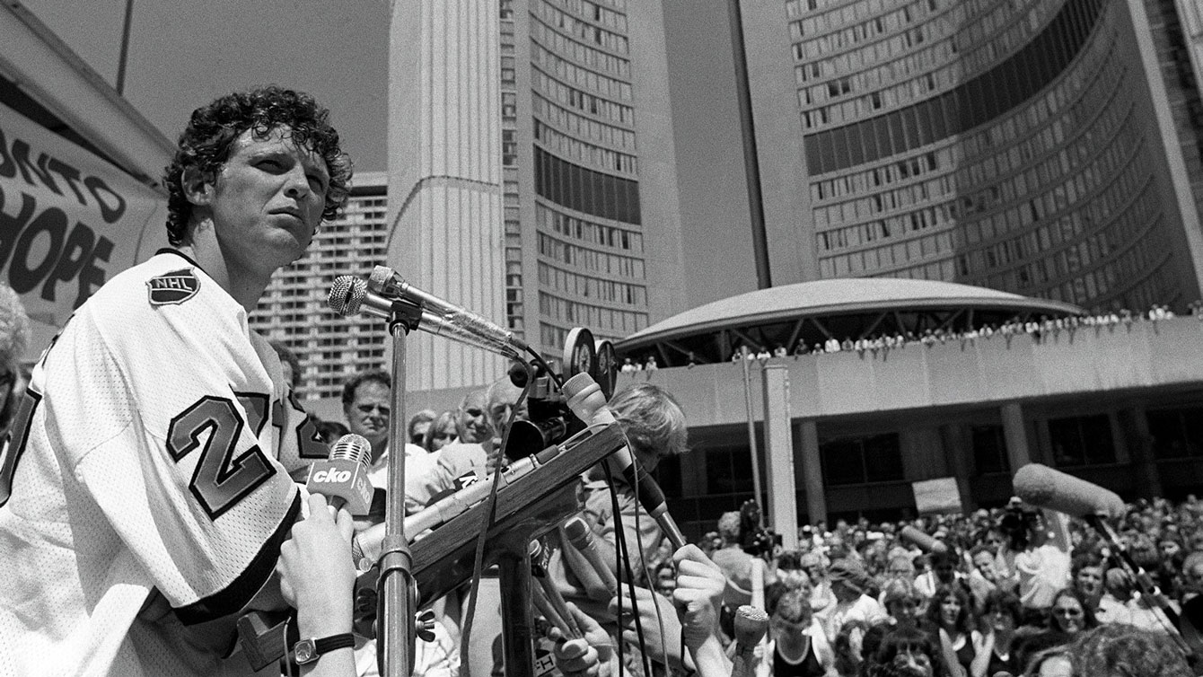 Terry Fox addresses the crowd at Nathan Phillips Square where a reported 10,000 people had gathered to watch him arrive in front of City Hall. Fox is wearing a Darryl Sittler NHL All-Star Game jersey, donated to him by the Toronto Maple Leafs legend who joined Fox on the run up University Avenue.