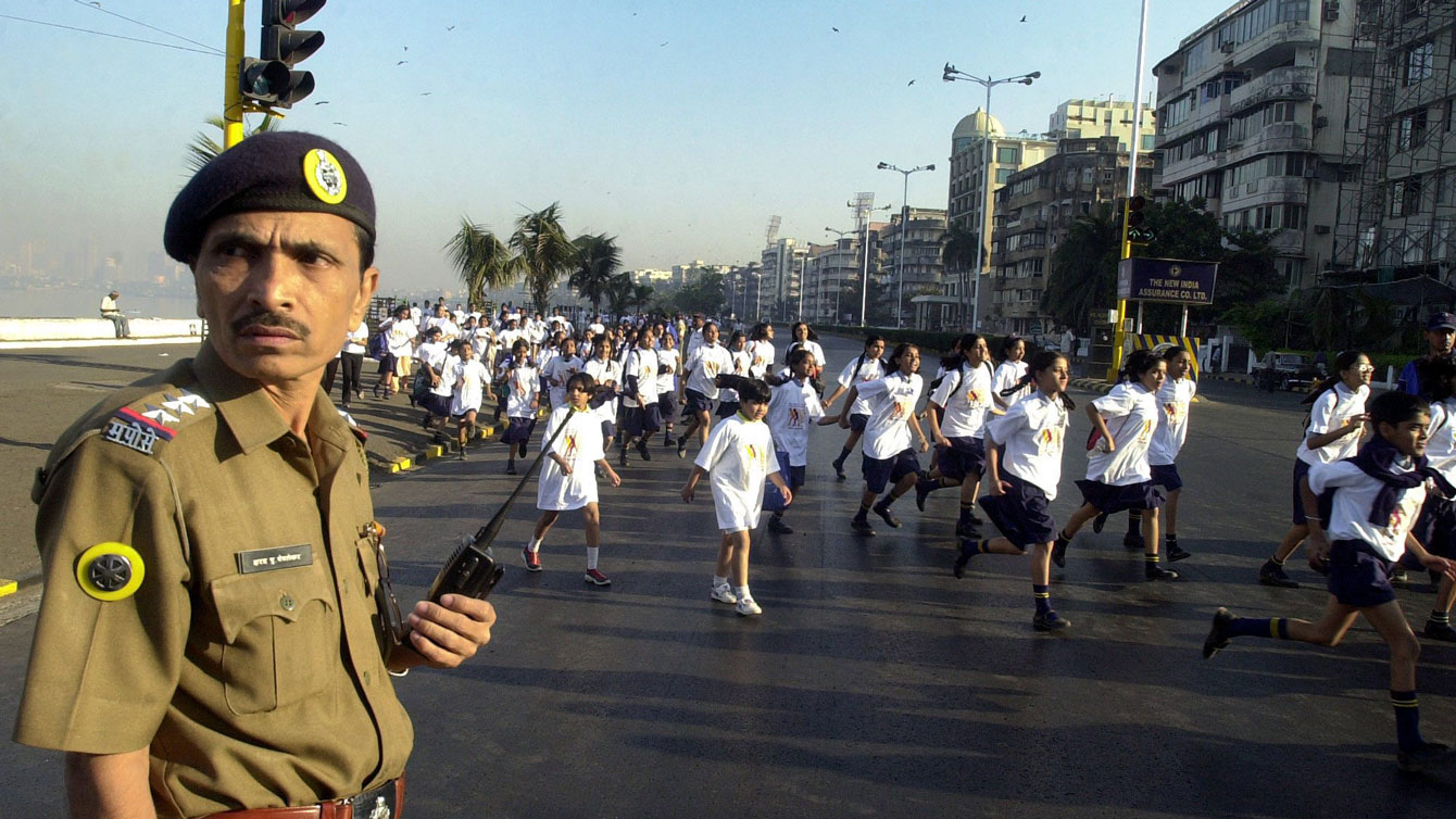 A police officer stands on guard as children take part in an international Terry Fox Run, Bombay, India in 2004.