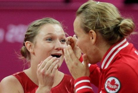Rosie MacLennan and Karen Cockburn react as gold medal scores arrive at London 2012.