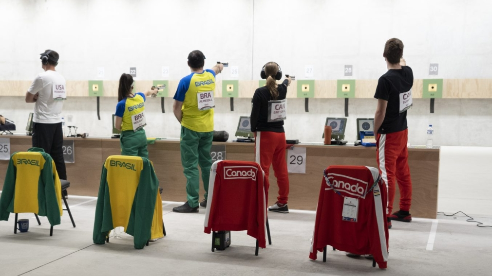 Four athletes aiming pistols at targets
