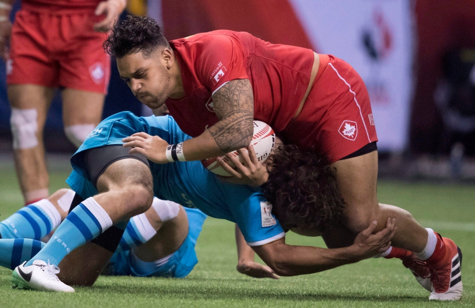 Mike Fuailefau of Canada tries to get past Diego Ardao of Uruguay during the World Rugby Seven Series at B.C. Place