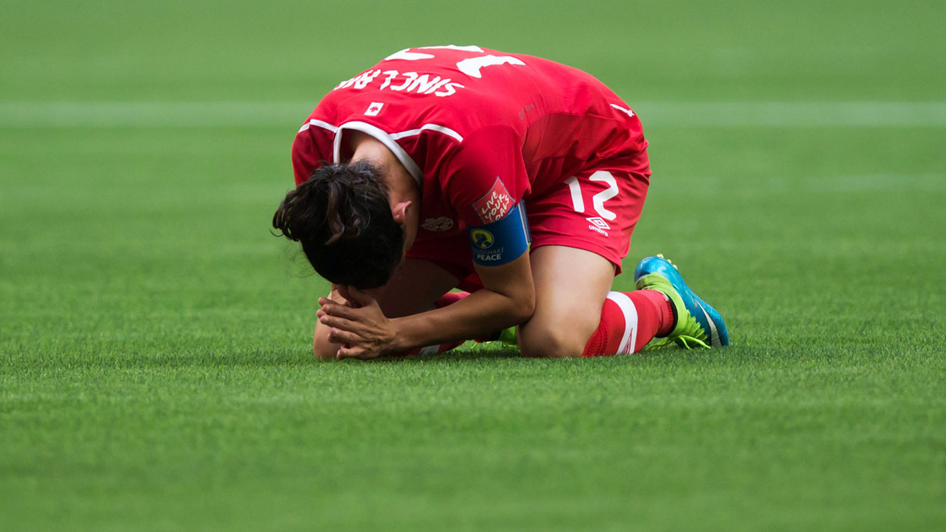 A dejected Christine Sinclair goes to ground at the final whistle as Canada loses 2-0 to England at the FIFA Women's World Cup on June 27, 2015.
