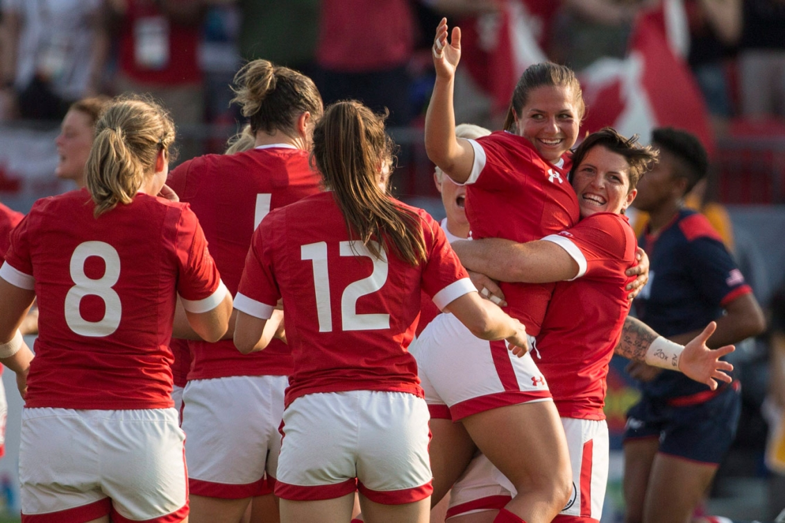The women gather to celebrate their 55-7 gold medal match trouncing of the USA. Brittany Benn (right), Ashley Steacy (second from right). (Photo: Canadian Press)